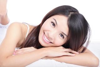 A woman lays down and smiles | Tooth Colored Fillings Hershey PA