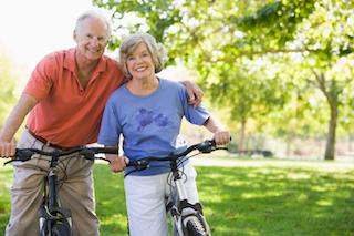 An elderly couple riding bikes and smiling together | Dental Implants Hershey PA