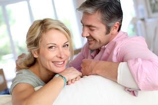 A woman and a man smile in a living room | Hershey PA dental implants