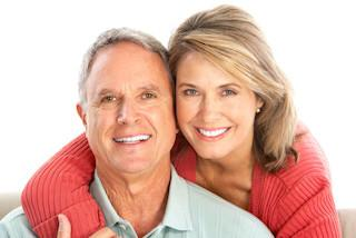 A couple smiles in front of a white backdrop | Periodontal Care Hershey PA
