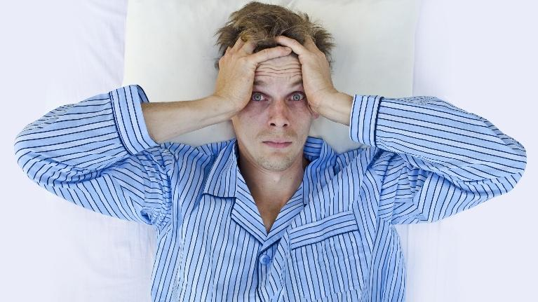 Man in bed looking stressed | Dentist Hershey PA