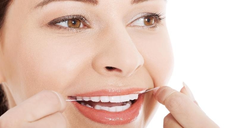 A woman flosses her teeth | hershey pa preventive dentist