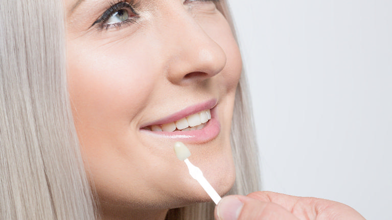 a woman getting a veneer compared to her teeth | veneers hershey PA