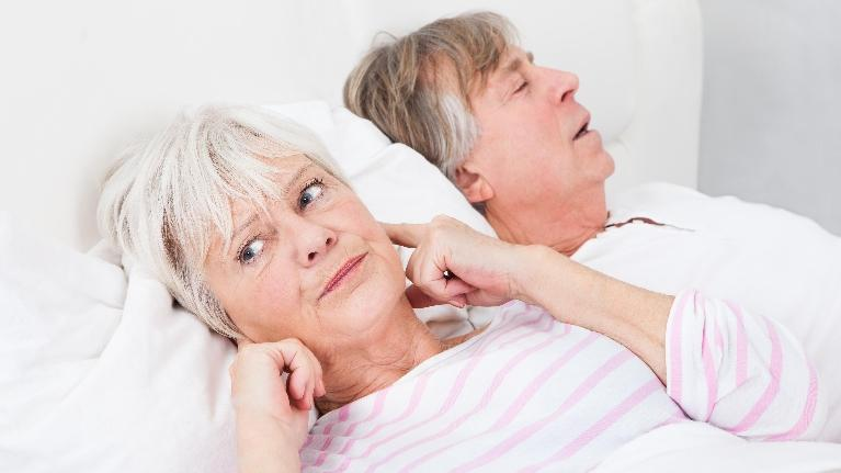 a woman plugs her ears next to her sleeping husband | hershey dentist