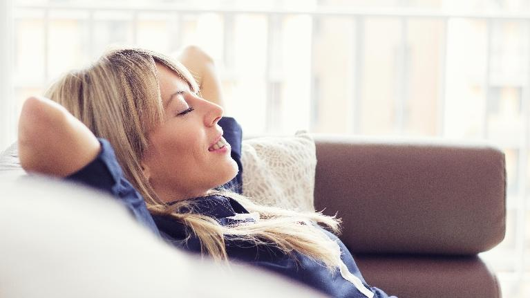 a woman relaxes on a couch | Hershey PA preventive dentist